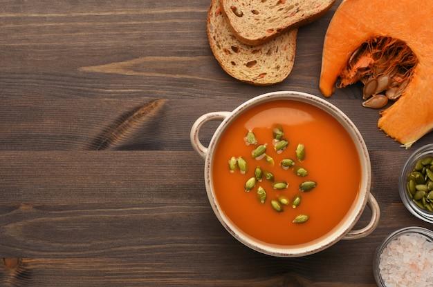 Soupe de potiron décorée de graines sur fond de bois vue de dessus. pain aux légumes, tranche de citrouille, graines et sel sur fond en bois avec place pour le texte.