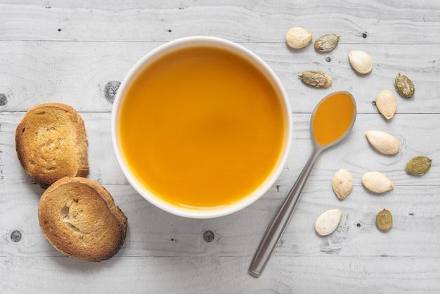 Soupe de potiron avec du pain sur une table en bois clair avec cuillère et graines