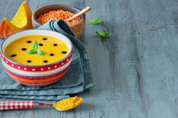 Soupe de potiron épicée aux lentilles rouges et au curcuma servie avec des feuilles de menthe et des gouttes de vinaigre balsamique
