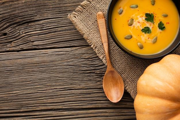 Soupe de potiron à plat dans un bol et une cuillère en bois avec espace de copie