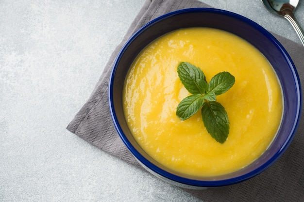 Soupe de potiron en purée d'épices dans une assiette bleue sur la table.
