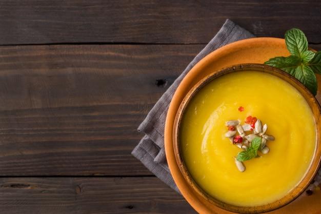 Soupe de potiron purée avec des épices dans des bols en bois sur des planches sombres.
