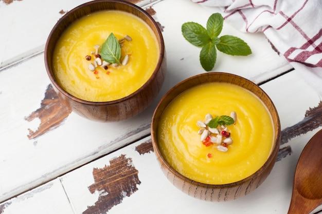 Soupe de potiron en purée avec des épices dans des bols en bois sur des tableaux lumineux.