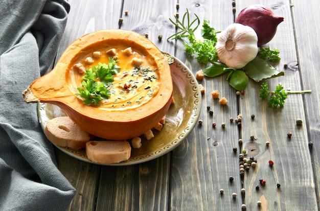 Soupe de potiron servie dans une citrouille évidée avec des croûtons
