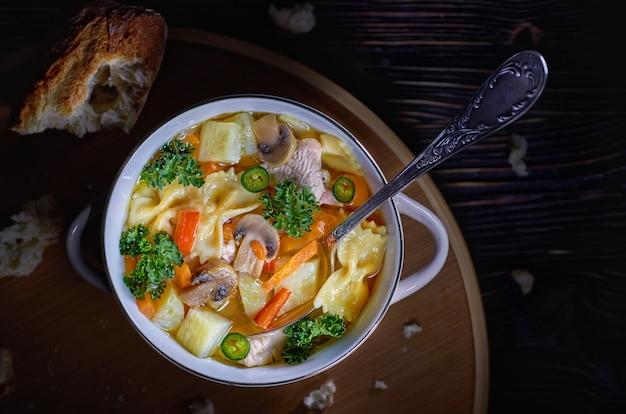 Soupe de poulet aux champignons et aux herbes dans un discret