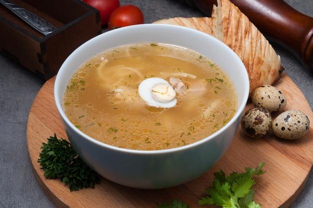 Soupe de poulet aux nouilles et œuf de caille sur une planche en bois