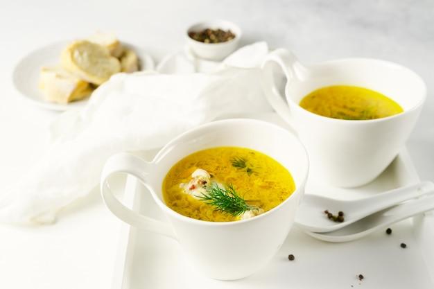Soupe de poulet aux pâtes maison servie dans des tasses