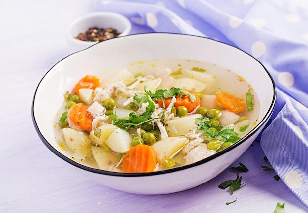 Soupe de poulet aux petits pois, carottes et pommes de terre dans un bol blanc