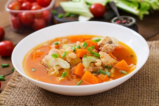 Soupe de poulet aux tomates avec citrouille, haricots et céleri dans un bol blanc