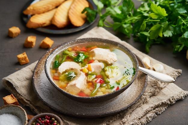 Soupe de poulet faite maison avec des légumes, croûtons, brocolis sur brun foncé