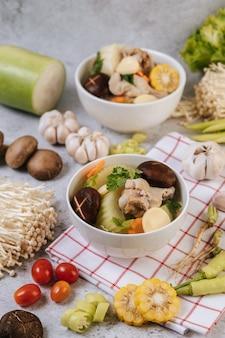 Soupe de poulet avec maïs, champignons shiitake, champignons enoki et carottes.