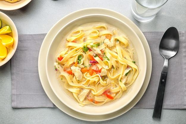 Soupe poulet et nouilles en assiette sur table de cuisine