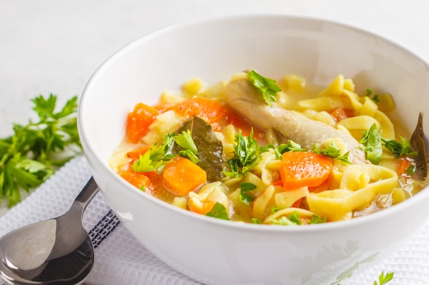 Soupe de poulet et nouilles et légumes dans un bol blanc sur fond blanc, espace de copie.