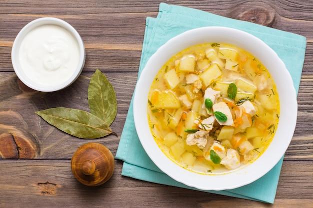 Soupe de poulet prête à l'emploi avec pommes de terre et herbes dans un bol blanc et crème sure sur une table en bois