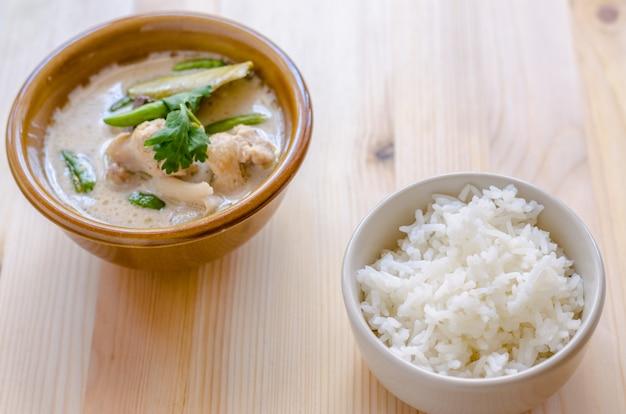 Soupe de poulet thaï au lait de coco (tom kha gai) avec du riz sur fond en bois, cuisine thaïlandaise.
