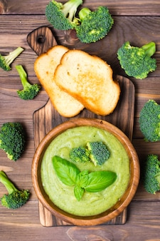 Soupe de purée de brocoli chaude prête à manger avec des tranches de brocoli et de feuilles de basilic dans une assiette en bois et des tranches de pain blanc grillé sur une planche à découper et des inflorescences de brocoli