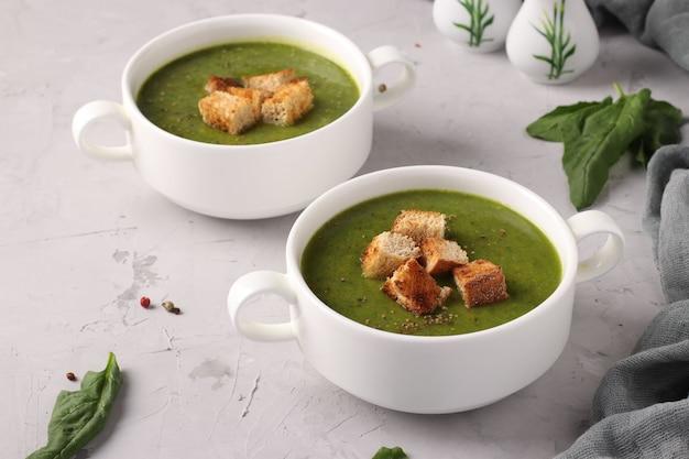 Soupe de purée d'épinards verts servie avec des croûtons dans deux bols blancs sur un fond de béton gris, gros plan