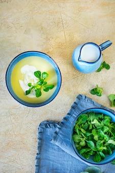 Soupe de purée maison de courgettes fraîches et d'épinards yang sur fond jaune clair.