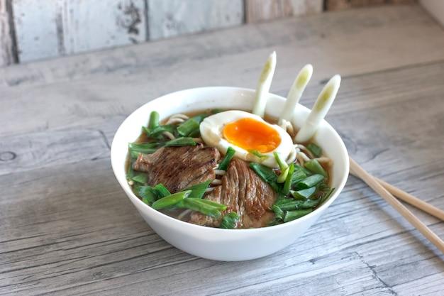 Soupe de ramen aux oignons frais, œuf à la coque et viande frite