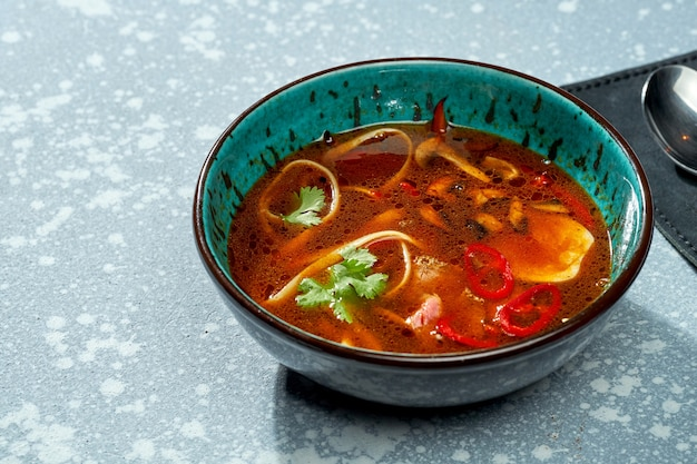 Soupe de ramen pan-asiatique épicée avec nouilles, viande, piments forts et coriandre dans un bol bleu sur fond gris