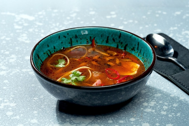 Soupe de ramen pan-asiatique épicée avec nouilles, viande, piments forts et coriandre dans un bol bleu sur une surface grise