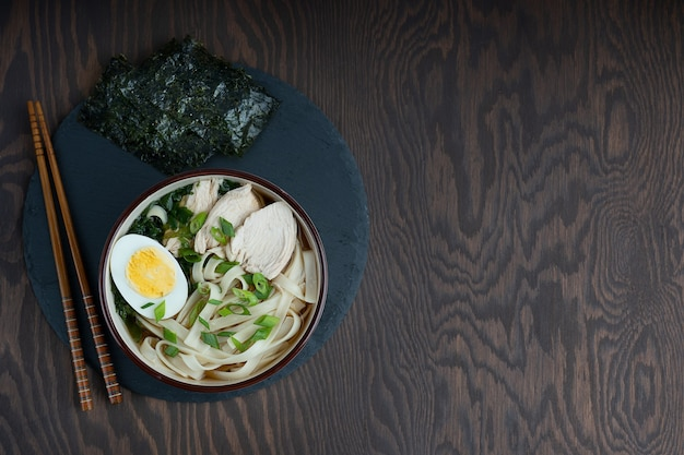 Soupe de ramen avec viande de poulet, nouilles, œuf dur dans un bol avec des baguettes sur table en bois