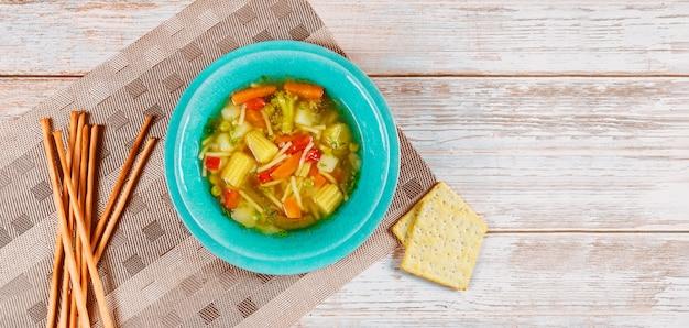 Soupe de régime avec des légumes sains, des craquelins et des bâtonnets de pain italien.