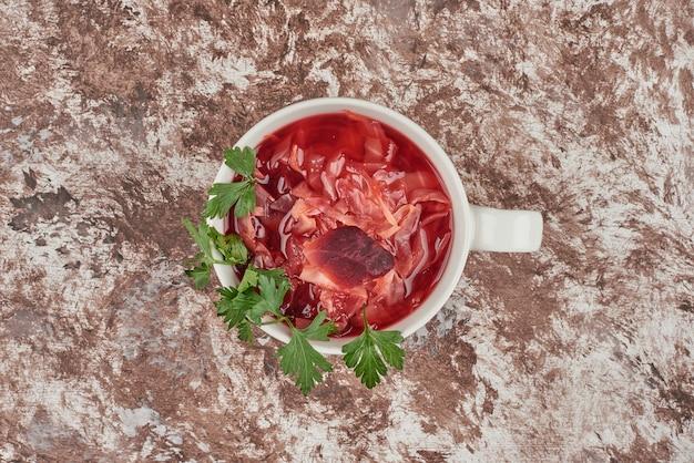 Soupe rouge aux herbes servie avec du pain.
