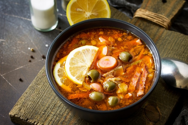 Soupe russe traditionnelle solyanka avec viande saucisses légumes câpres style rustique