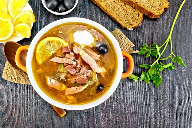 Soupe salée au citron, viande, cornichons, olives à la sauce tomate dans un bol sur un sac, pain sur fond de planche de bois d'en haut