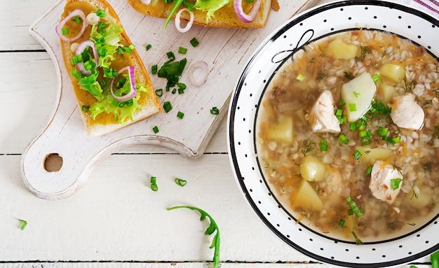 Soupe de sarrasin avec du poulet dans une assiette, pain à la moutarde et un oignon rouge sur une table en bois blanche. vue de dessus
