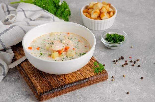 Soupe de saumon à la crème, pommes de terre, carottes, herbes et croûtons dans un bol sur un fond de béton gris. copiez l'espace.