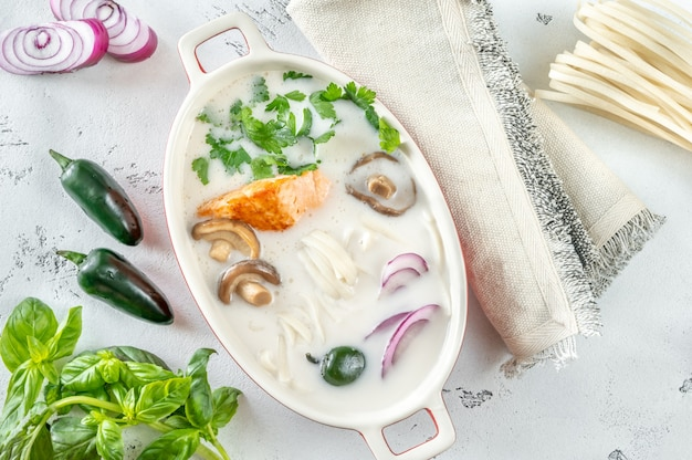 Soupe de saumon thaï à la noix de coco avec des ingrédients à plat