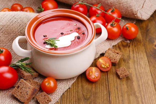 Soupe savoureuse aux tomates sur table en bois