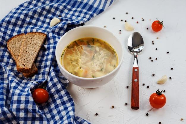 Soupe savoureuse et nutritive composée de nouilles, de carottes et de pommes de terre sur la table blanche décorée avec une serviette bleue, une cuillère, deux pois de pain, des tomates et du poivre. délicieux déjeuner.