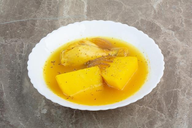 Soupe savoureuse avec de la viande de poulet et des pommes de terre sur une assiette blanche.