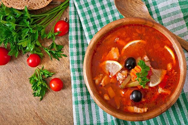 Soupe solyanka russe avec de la viande, des olives et des cornichons dans un bol en bois