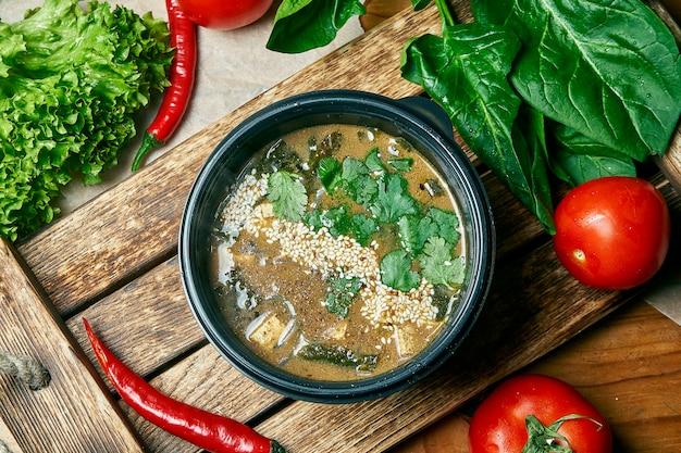 Soupe thaï végétarienne avec pâte de miso, tofu, nori, graines de sésame et persil dans un bol noir sur une table en bois. vue de dessus plat jeter la nourriture