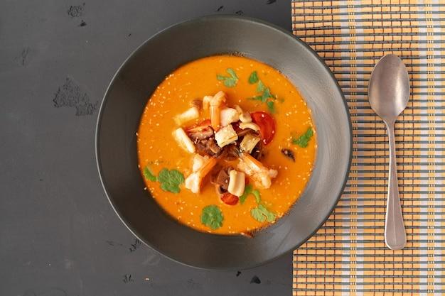 Soupe thaïlandaise tom yam dans un bol noir servi sur fond gris