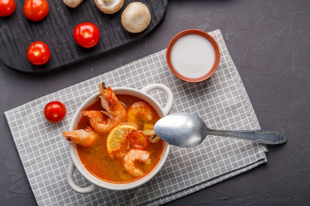 Soupe de tom yam aux crevettes dans une assiette sur la table sur une serviette à côté de champignons et de tomates. photo horizontale