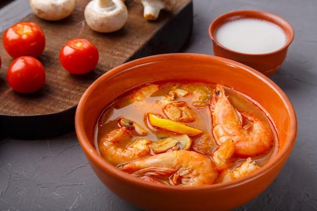 Soupe de tom yam aux crevettes dans une soupière sur un fond de béton à côté d'un bol avec des champignons au lait de coco et des tomates. photo horizontale