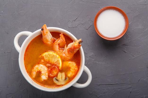 Soupe tom yam aux crevettes dans une soupière sur un fond de béton à côté d'un bol de lait de coco. photo horizontale