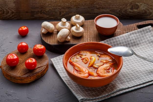 Soupe tom yam aux crevettes dans une soupière sur une serviette sur un fond de béton à côté d'un bol avec des champignons au lait de coco et des tomates