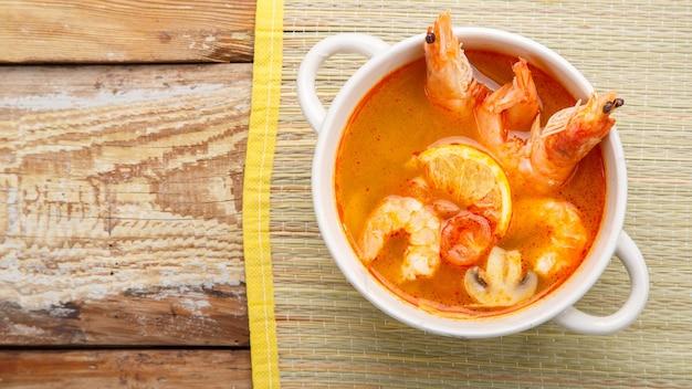 Soupe tom yam aux crevettes dans une soupière sur un tapis sur une table en bois. photo horizontale