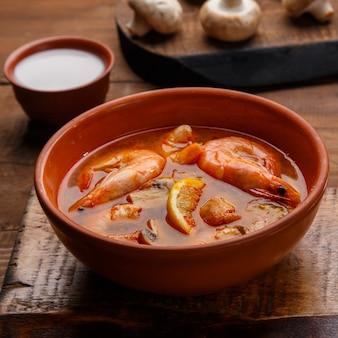 Soupe de tom yam aux crevettes et lait de coco dans une assiette square photo