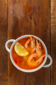 Soupe tom yam aux crevettes et lait de coco sur une table en bois. photo verticale