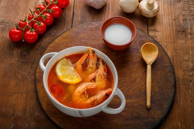 Soupe tom yam aux crevettes et lait de coco sur la table sur une planche ronde à côté de champignons au lait de coco et de tomates. photo horizontale