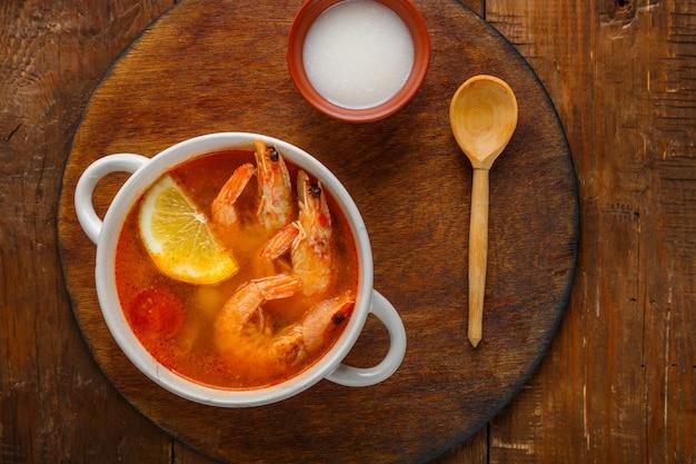 Soupe tom yam aux crevettes et lait de coco sur la table sur une planche ronde à côté du lait de coco et d'une cuillère. photo horizontale