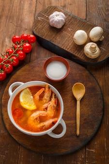 Soupe tom yam aux crevettes et lait de coco sur la table sur une planche ronde à côté du lait de coco et des tomates.