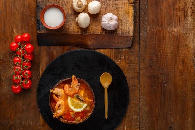 Soupe tom yam aux crevettes et lait de coco sur la table sur une planche ronde près des champignons au lait et des tomates. photo horizontale